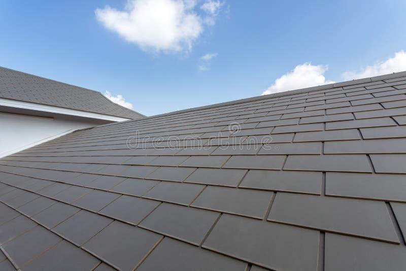 Kritisera taket mot blå himmel, gråa det hous tegelplattataket av konstruktion arkivbilder