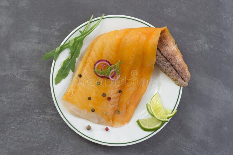 Kritiserar den härlig guling rökte koljafiskfilén på en platta med en filial av ny arugula, limefrukt och rosa färgbäret på grå f royaltyfri foto