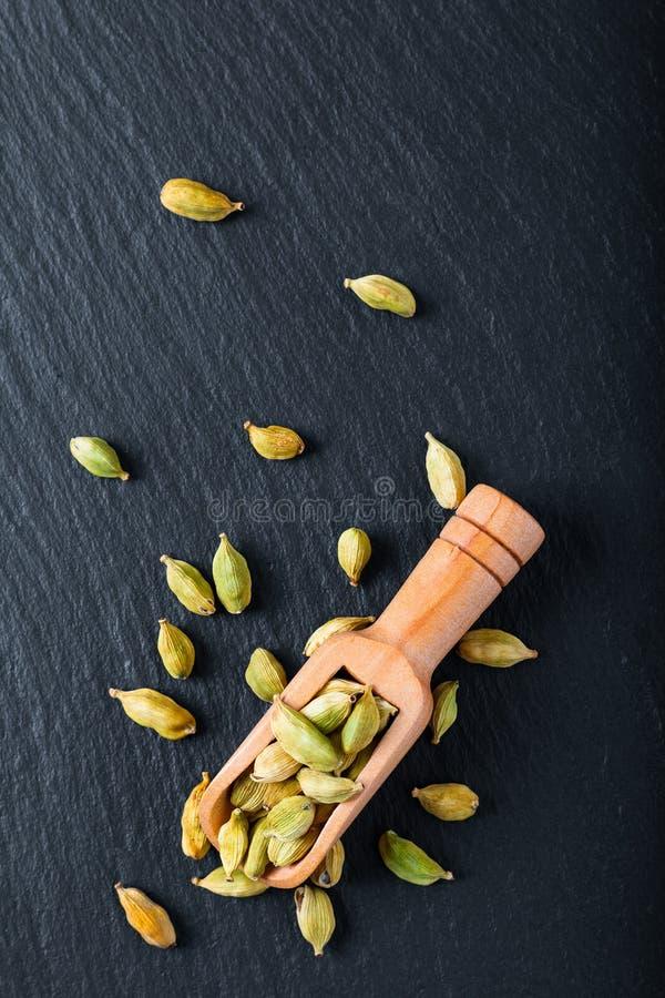 Kritiserar den organiska kardemumman för exotiska kryddor i bambuskopa på svart stenbakgrund royaltyfri fotografi