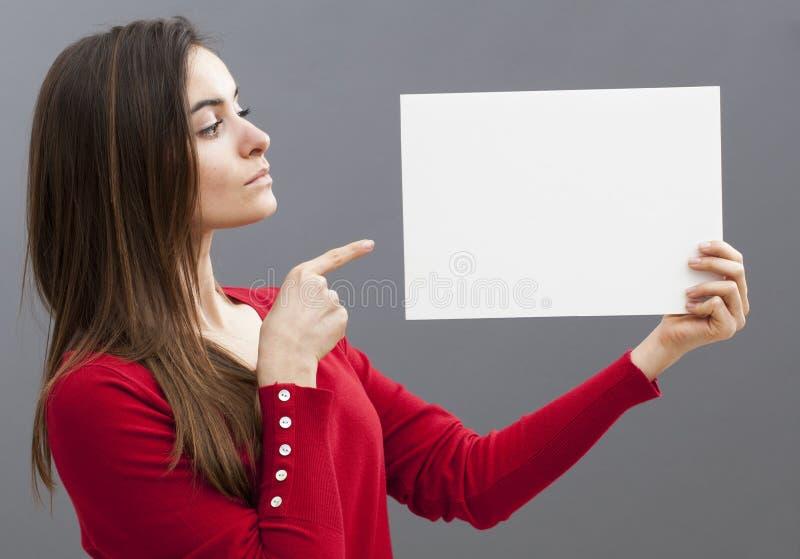Kritisk 20-talflicka med långt hår som ombord pekar på ett meddelande med vit bakgrund royaltyfri bild