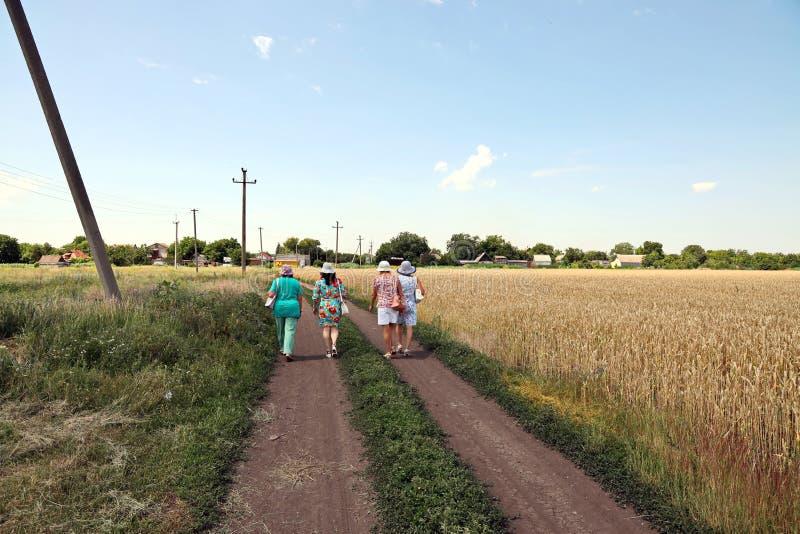 Krivoy Rog, Ucrânia, junho de 22.2019 Mulheres caminhando pela estrada rural e pelo campo de trigo fotografia de stock
