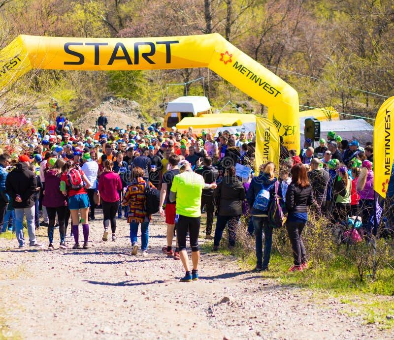 Krivoy Rog, Ukraina - 21 April, 2019: Grupp av unga idrottsman nen i startposition F?rdiga ungdomarsom f?rbereder sig f?r maraton arkivfoton
