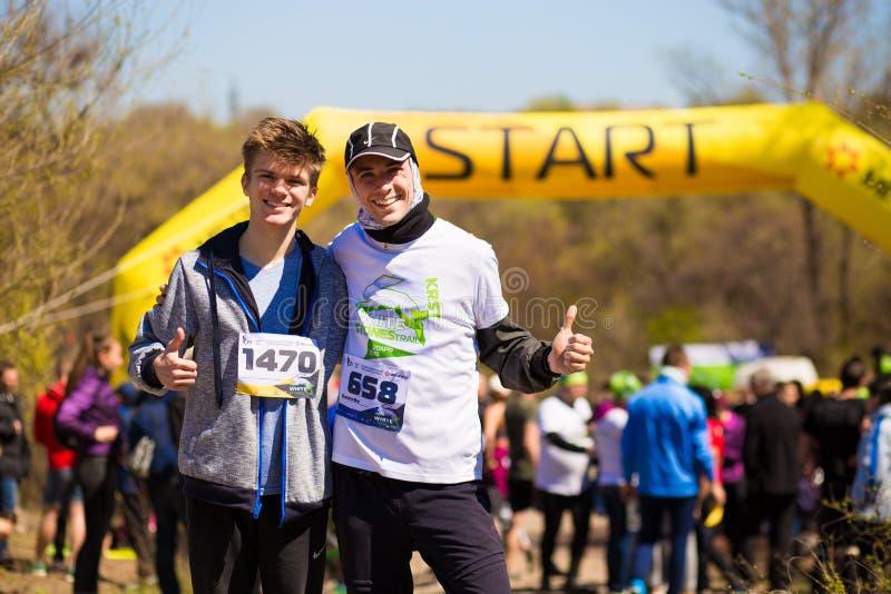 Krivoy Rog, Ukraina - 21 April, 2019: Grupp av unga idrottsman nen i startposition F?rdiga ungdomarsom f?rbereder sig f?r maraton royaltyfria foton