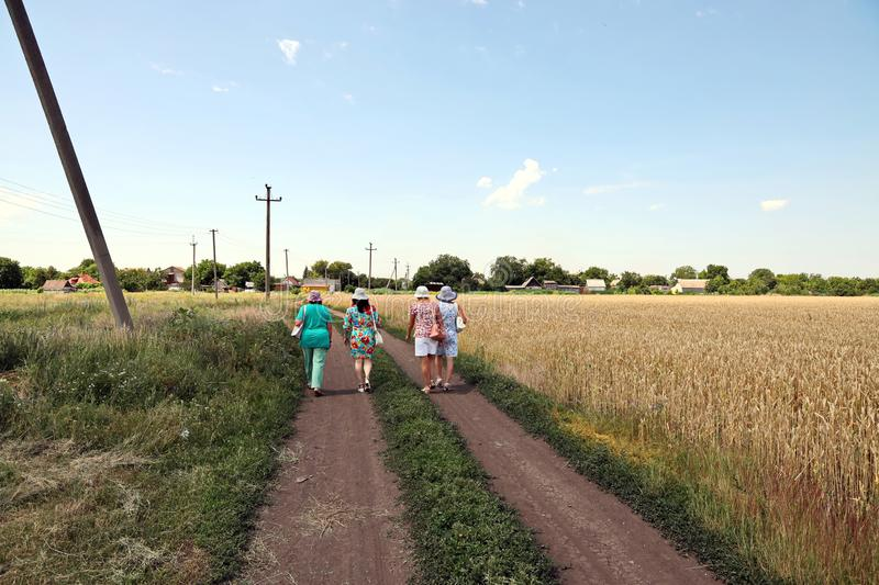 Krivoy Rog, Ukraine, June, 22,2019. Women walking along a rural road and wheat field. Summer stock photography