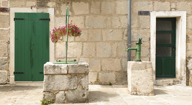 Kroatië, de zomerlandschap: een binnenplaats van een oud steen Dalmatisch bastion met goed en een waterkolom stock afbeeldingen