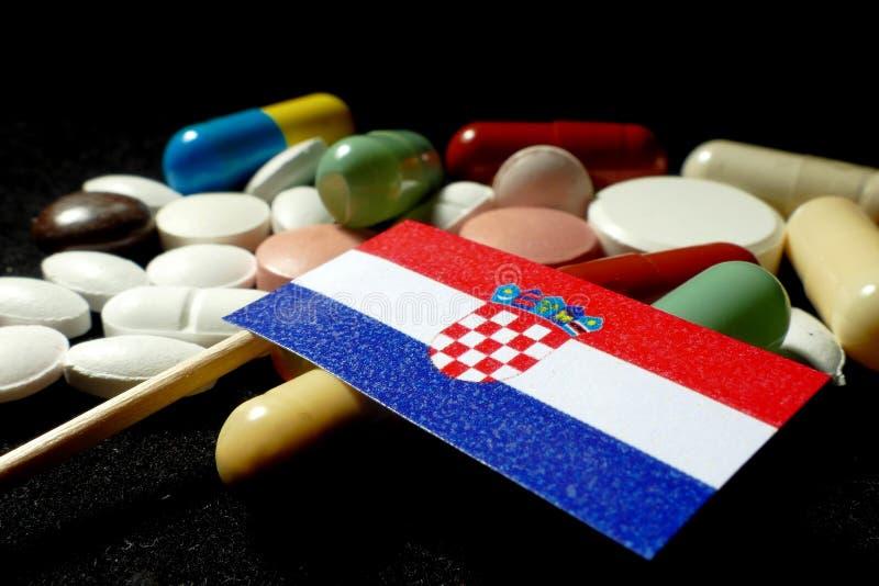 Kroatisk flagga med lotten av medicinska preventivpillerar som isoleras på svart backgr fotografering för bildbyråer