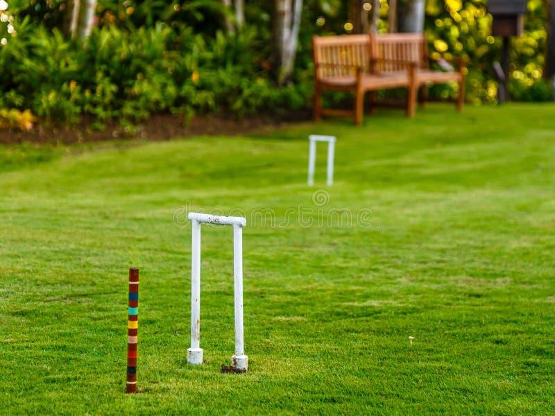 Kroketttor und -stange auf Grasrasen mit Holzbank und Garten im Hintergrund lizenzfreie stockfotografie