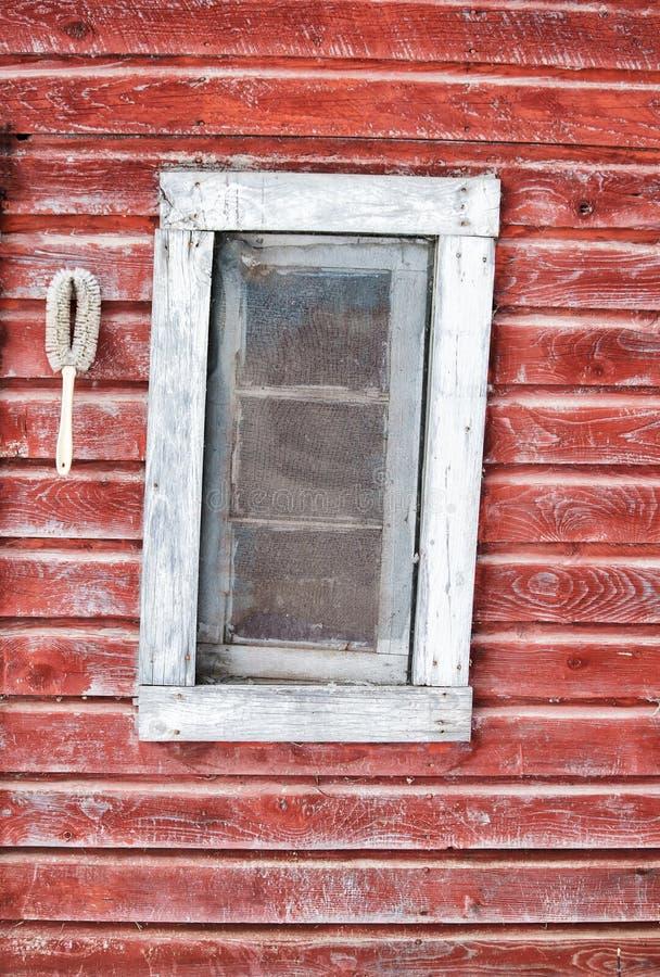 Krokigt fönster i röd urblekt vägg royaltyfria bilder