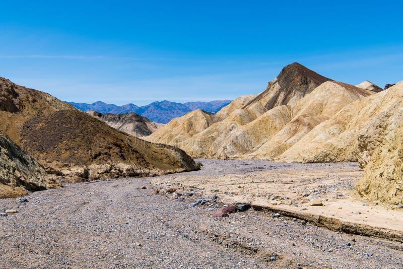 Krommen van een de droge rotsachtige rivierbed door een onvruchtbaar woestijnlandschap van kleurrijke badlands en pieken royalty-vrije stock fotografie