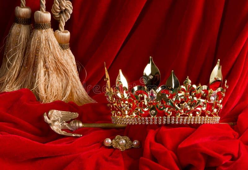 Krona och spira på röd sammet arkivfoton