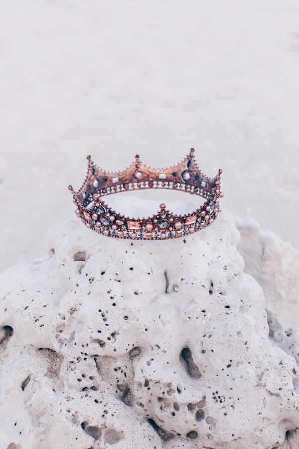 Krona som ligger på stenen på stranden arkivbild