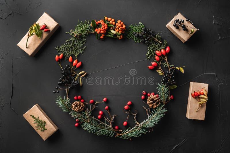 Krone von Weihnachtsbaumasten, Kiefernkegel, Beeren, Walnüsse, Geschenke, auf schwarzem Steinhintergrund lizenzfreie stockbilder