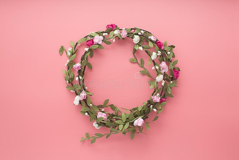 Kronen van bloemen en bladeren op een roze achtergrond Vlak leg, kopieer ruimte, hoogste mening Bloemensamenstelling royalty-vrije stock fotografie