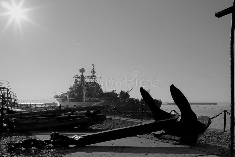 Kronstadt, Rusland, Oktober 2018 Oud schipanker op de pijler en het silhouet van het schip in de stralen van de zon royalty-vrije stock fotografie