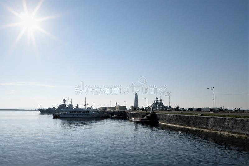 Kronstadt, Rusland, Oktober 2018 Schepen en boten bij de pijler dichtbij de vuurtoren bij zonsondergang stock fotografie