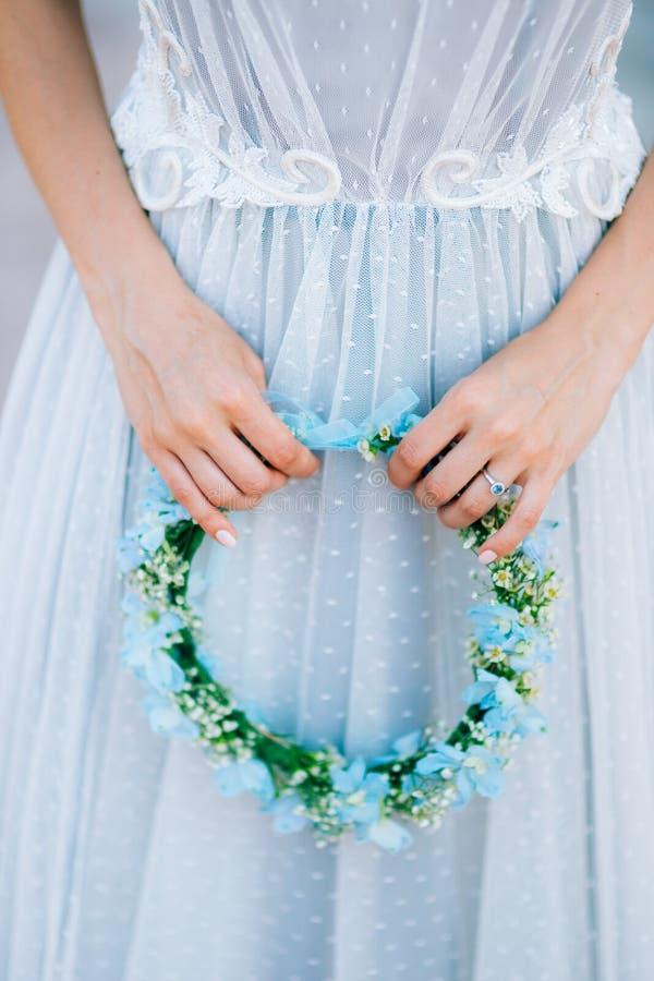 Kroon op een hoofd van blauwe en witte bloemen in bruid` s hand i stock foto