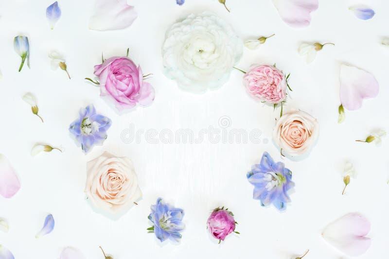 Kroonkader met roze en roomrozen, witte ranunculus, blauwe riddersporen, witte acacia en bloemblaadjes van ridderspoor en royalty-vrije stock afbeeldingen