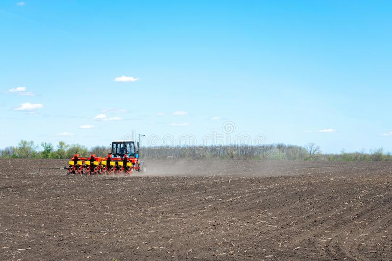 Kropivnitskiy,乌克兰– 12可以,2018年:拖拉机在一好日子播种在一个被犁的领域的玉米 拖拉机播种-播种庄稼在 免版税库存图片