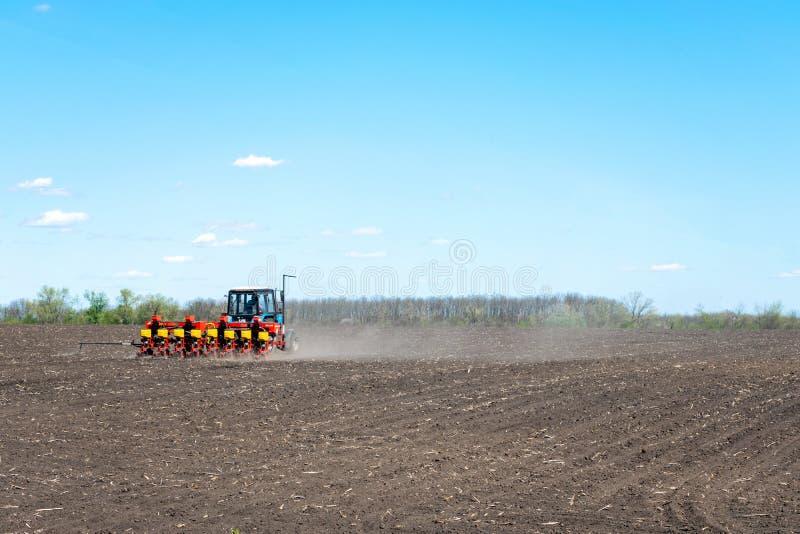 Kropivnitskiy, de Oekraïne – 12 kunnen, 2018: de tractor zaait graan op een geploegd gebied op een zonnige dag tractor het zaaien royalty-vrije stock afbeelding