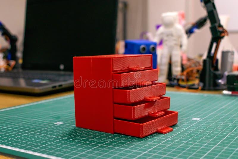 Kropivnitskiy Ukraina – 12 kan, 2018: 3D skrivev ut den röda plast- skänken på bakgrunden av bärbara datorn och apparater M?blema royaltyfri foto
