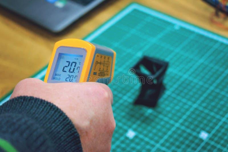 Kropivnitskiy, Ukraina – 12 mogą, 2018: Laserowy termometr Żółty pirometr w mężczyzna ręce Pirometr, przyrząd dla mierzyć obrazy royalty free