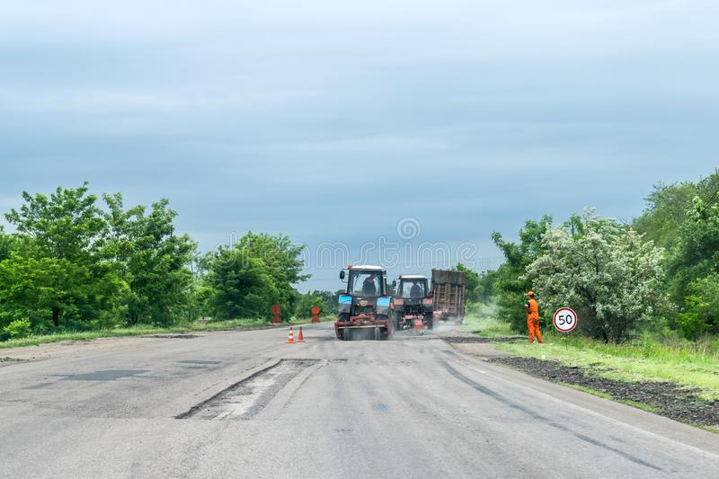 KROPIVNITSKIY, UKRAINE – 27 MAY, 2018: Road repair concept. Road construction equipment and Workers on highway. Tractors, truck. S, roller on the road royalty free stock photo