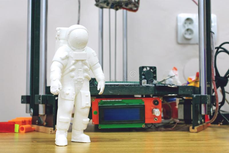 Kropivnitskiy, Ukraine – 12 may, 2018: 3D printed astronaut, cosmonaut on the background of three dimensional 3d printer. Spaceman model printed on stock photography