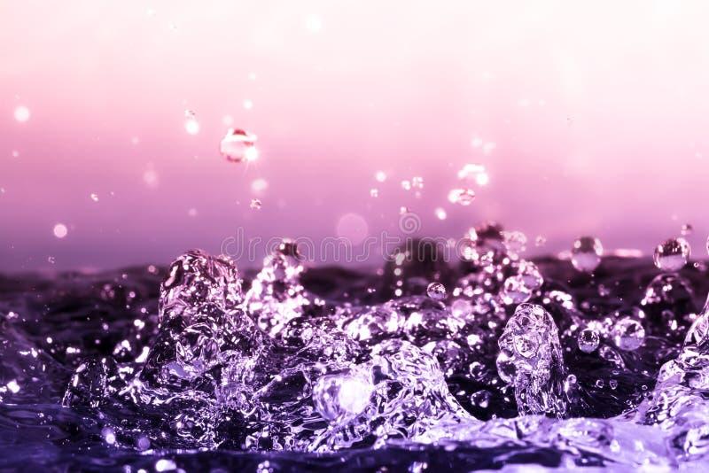 Krople woda w górę makro- z światło słoneczne spadkiem na ciężkiej pluśnięcie wody powierzchni na pięknym tle z gradientem fotografia stock