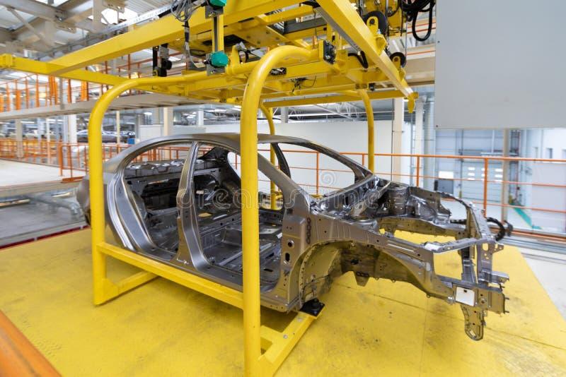 Kropp av bilen på den moderna enheten för transportör av bilar på växten automatiserad byggandeprocess av bilkroppen royaltyfri fotografi