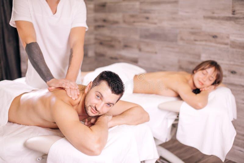 Kroppbehandling massageterapeut som ger massage till unga par arkivbilder