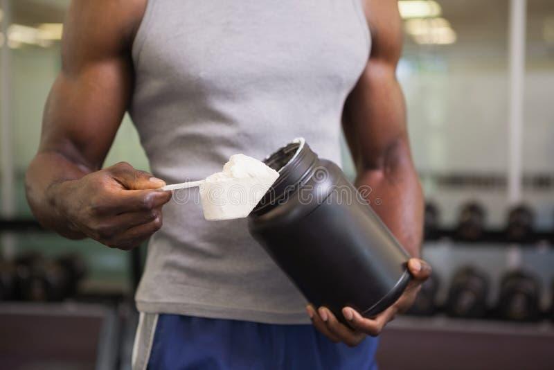 Kroppbyggmästare som rymmer en skopa av proteinblandningen i idrottshall fotografering för bildbyråer