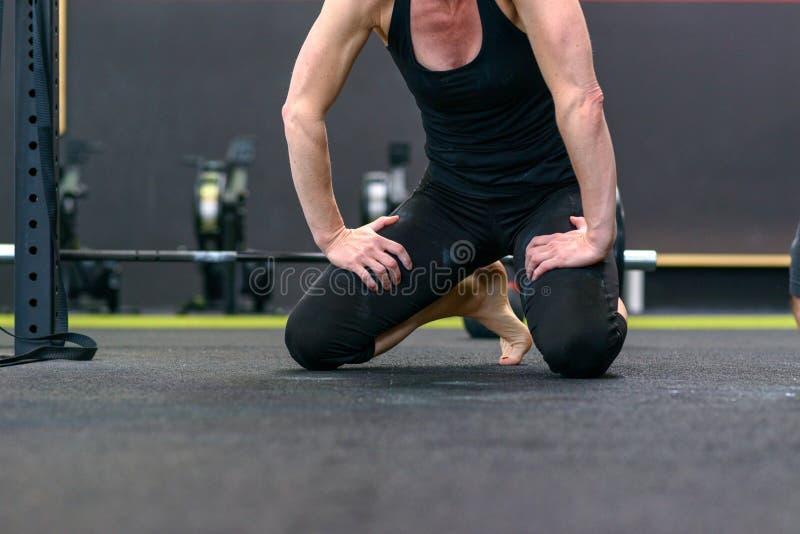 Kroppen av en barfota passform tonade kvinnan i en idrottshall royaltyfria bilder