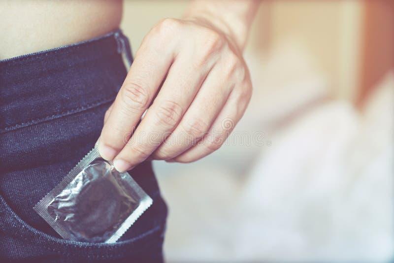 Kroppen för den unga mannen tar av skjortan fack för främre sida för jeans som bär kondomar som tar i handkondom från jeans royaltyfri foto
