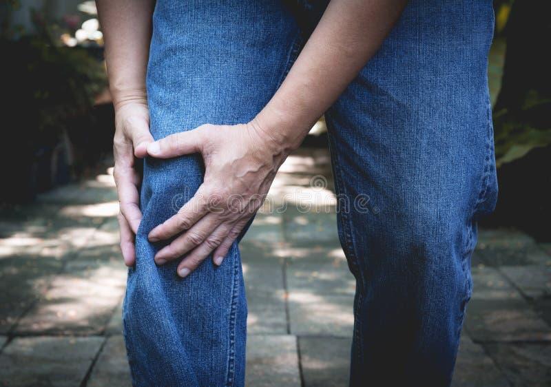 Kroppen smärtar smärtar den manliga kroppen för närbilden med i knä Mannen räcker att trycka på och att massera fotografering för bildbyråer
