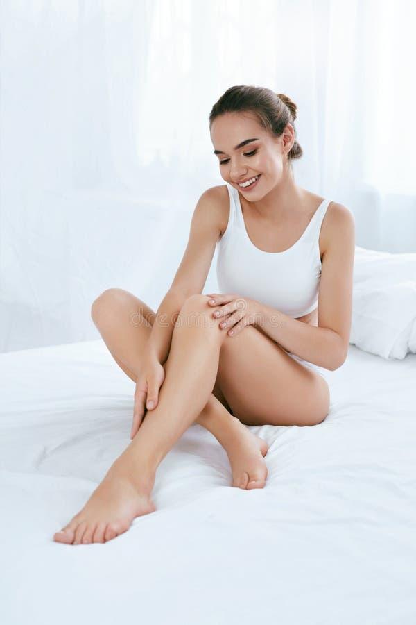 Kropphudomsorg Härlig kvinna som trycker på långa ben på vit säng royaltyfri foto