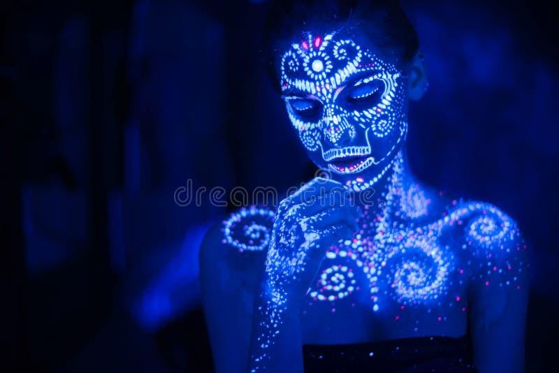 Kroppkonst p? kroppen och handen av en flicka som gl?der i det ultravioletta ljuset fotografering för bildbyråer