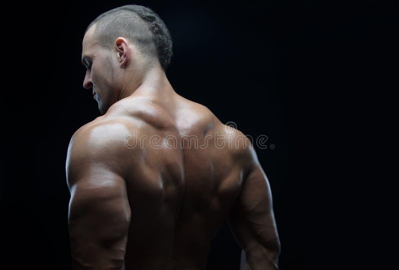 Kroppsbyggare- och remsatema: härligt med den pumpade nakna mannen för muskler som poserar i studion på en mörk bakgrund arkivbilder