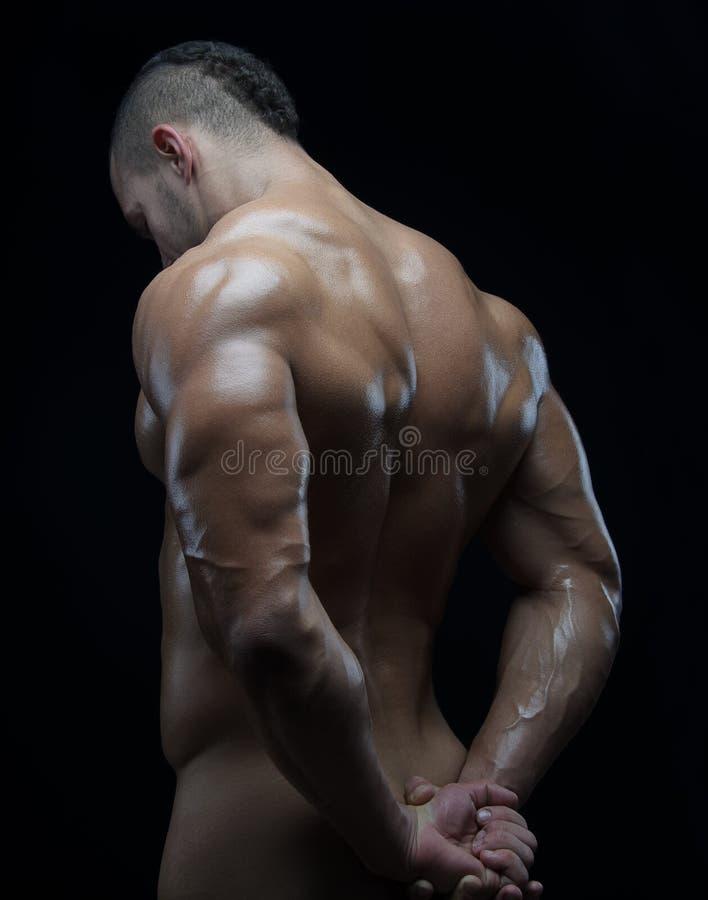 Kroppsbyggare- och remsatema: härligt med den pumpade nakna mannen för muskler som poserar i studion på en mörk bakgrund royaltyfria bilder