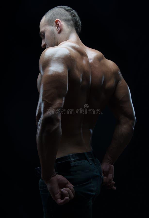 Kroppsbyggare- och remsatema: härligt med den pumpade nakna mannen för muskler som poserar i studion på en mörk bakgrund royaltyfri fotografi