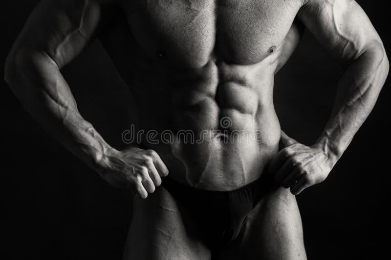 Kroppsbyggare på svart bakgrund arkivbilder