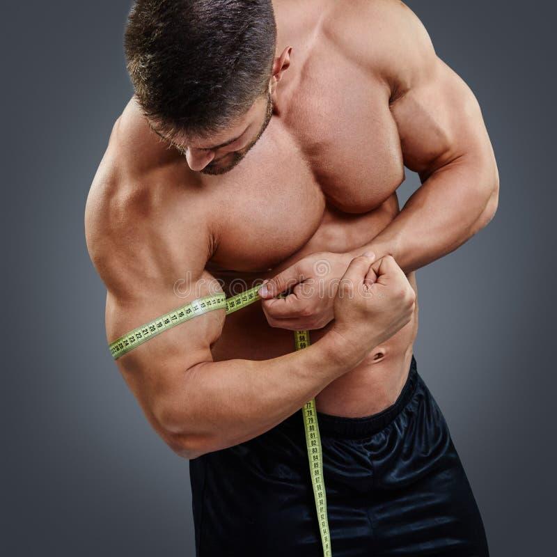Kroppsbyggare som mäter biceps med måttband arkivfoto