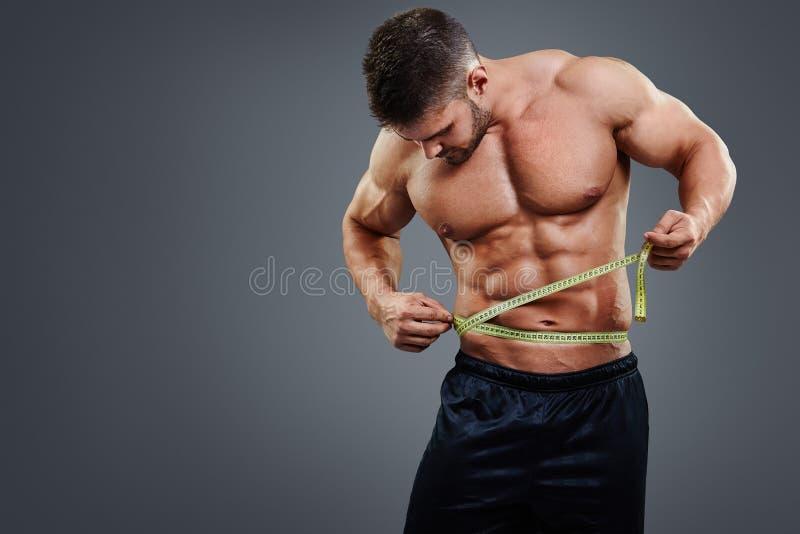Kroppsbyggare som mäter midjan med måttband royaltyfri bild