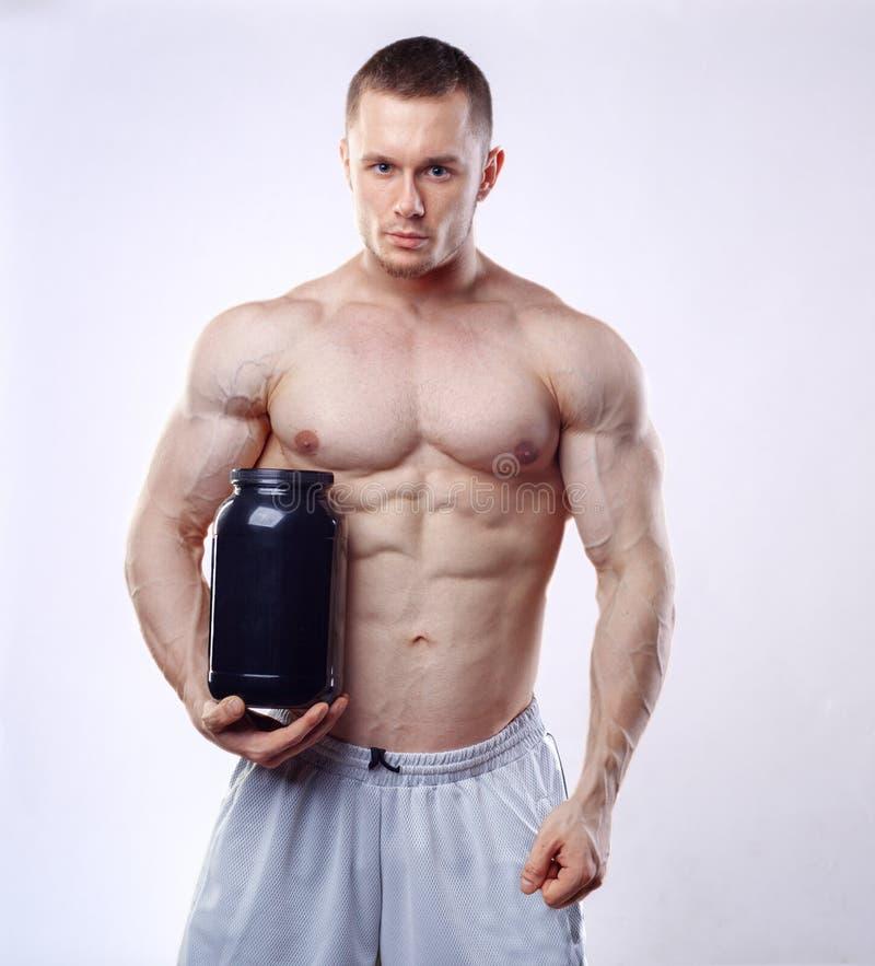 Kroppsbyggare som rymmer en svart plast- krus med vasslaprotein på vit bakgrund royaltyfria bilder