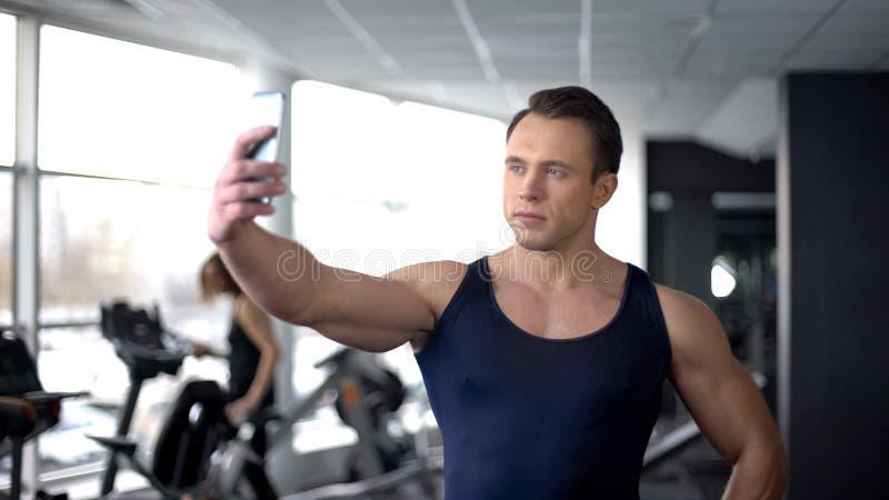 Kroppsbyggare som tar selfie i idrottshall och överför vid smartphonen, modern teknologi arkivbild
