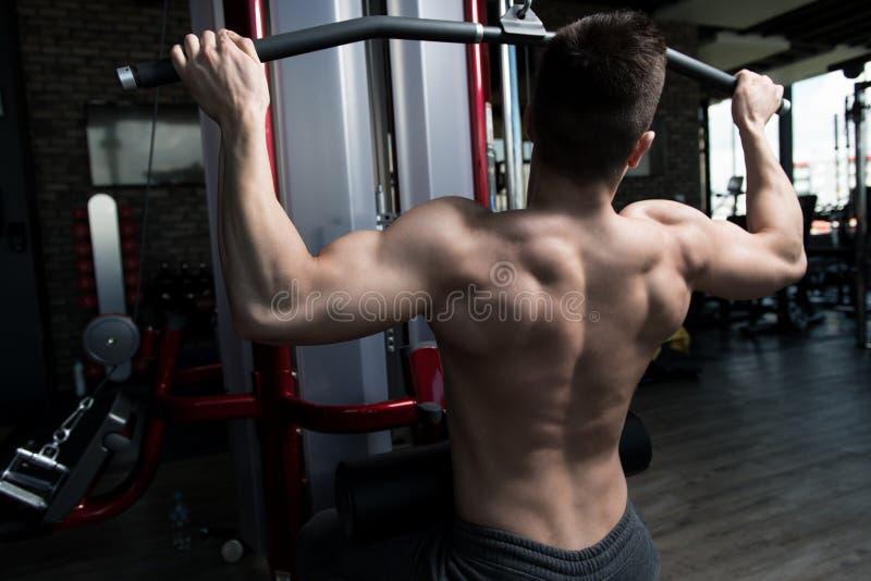 Kroppsbyggare som tillbaka övar i idrottshall arkivbilder