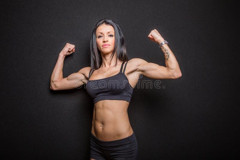 kroppsbyggarekvinnlig som slader muskler royaltyfria bilder
