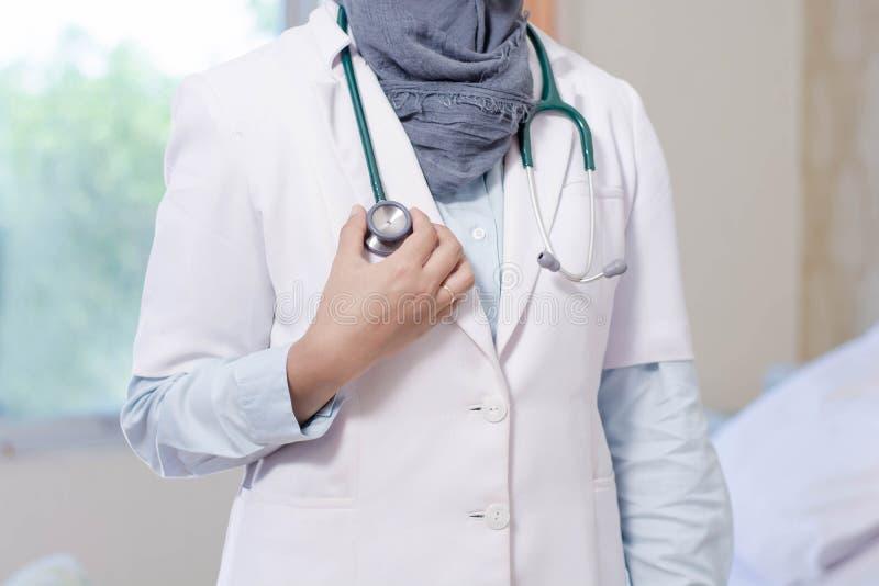 Kroppsdel för främre sikt av för doktorshand för hijab det kvinnliga huvudet för stetoskop för innehav inom ett sjukhusrum genom  arkivfoto