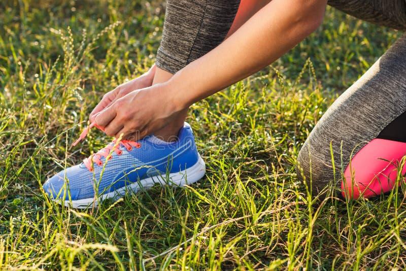 Kroppsdel: Idrottskvinnan binder skosnöre på hennes skor royaltyfri fotografi