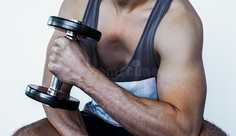 Kroppsdel och muskel av en man med hanteln fotografering för bildbyråer