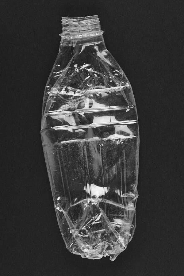 Krossad plast- flaska med svart bakgrund Återanvänd avskräde royaltyfri bild